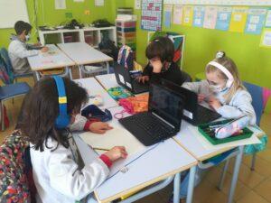 """Alumnes de 2n de primària de l'escola FEDAC Pineda en plena videoconferència amb els seus padrins lectors del projecte """"Històries compartides""""."""