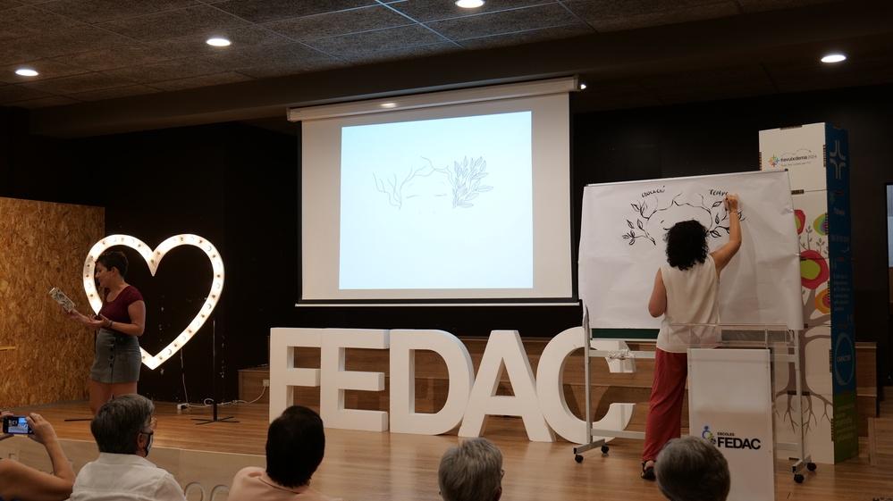 Les artistes Yèssica Ayala i Sílvia Morilla durant la seva creació conjunta de poesia i il·lustració en l'acte de comiat als educadors FEDAC jubilats.